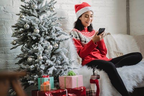 Happy woman using smartphone near Christmas tree