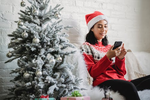 Happy young female in Santa hat and red jumper sitting on sofa near decorated Christmas tree and browsing mobile phone