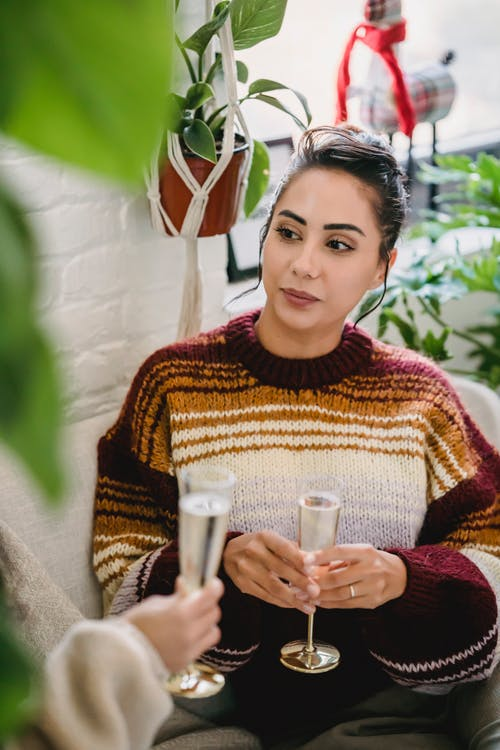Young Hispanic female in cosy knitted jumper and with glass of champagne sitting and talking to friend while celebrating holiday