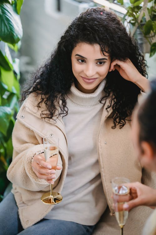 Cheerful young Hispanic female in casual clothes drinking wine celebrating holiday with friends