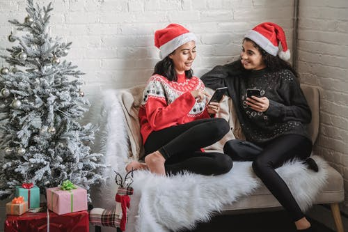 Cheerful women using smartphones while celebrating Christmas holiday at home