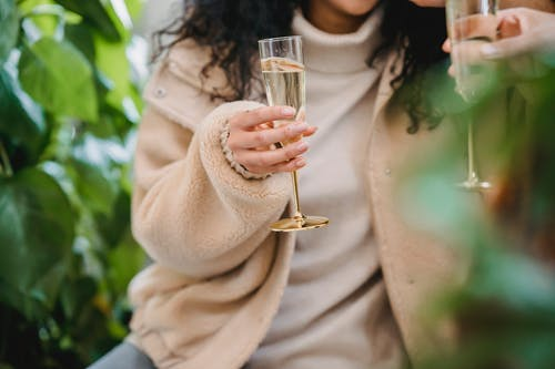 Anonymous female in smart casual clothes with glass of champagne celebrating occasion with friend