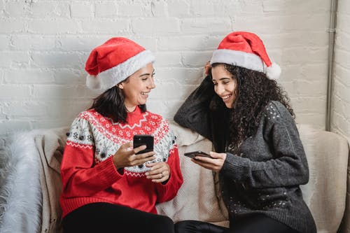 Happy young women using smartphones while spending Christmas holiday together