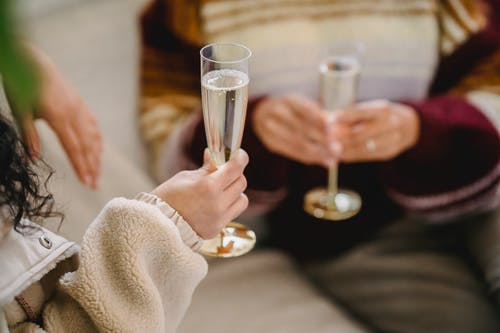 Unrecognizable women in casual clothes celebrating holiday sitting on sofa with glasses of champagne