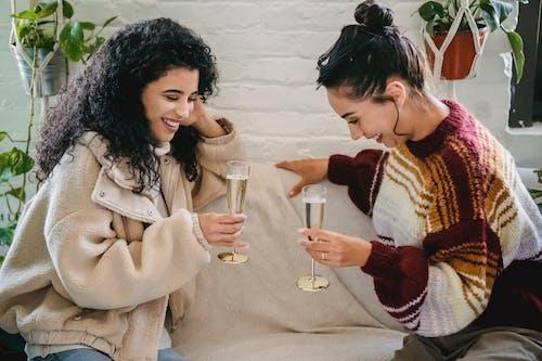 飲用グラスを保持しているベージュのコートの女性