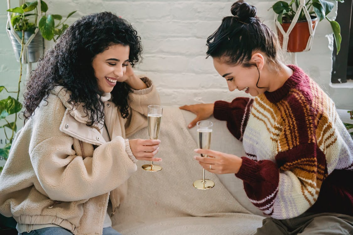 Young happy Hispanic female friends with glasses of champagne having fun sitting on sofa and celebrating holiday
