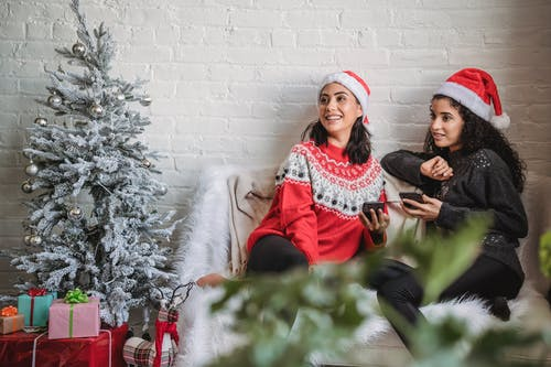 Happy young Hispanic women in Santa hat with mobile phones sitting on small sofa near decorated Christmas tree and looking away