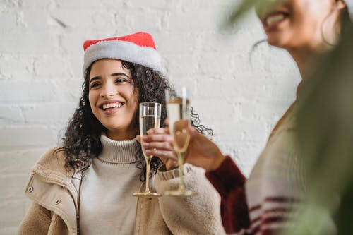Happy young women toasting with champagne on Christmas party