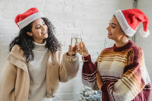 Smiling ethnic female friends toasting with champagne glasses while congratulating each other with New Year