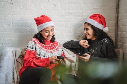 Cheerful ethnic women in Santa hats using smartphones at Christmas