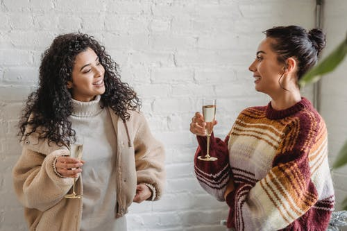 Positive ethnic girlfriends drinking champagne while celebrating holiday and talking to each other