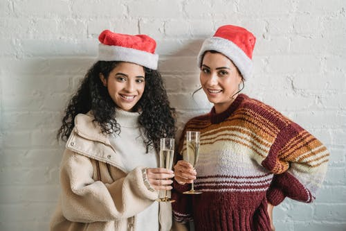 Cheerful ethnic female friends wearing knitted sweaters and Santa hats standing close while celebrating Christmas together