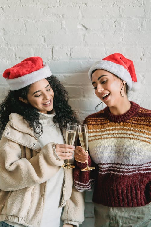 Smiling ethnic friends clinking champagne glasses during Christmas party