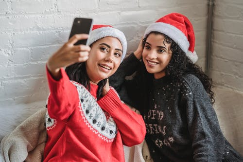 High angle of ethnic best friends in Santa hats smiling widely while taking photo on cellphone during New Year holidays