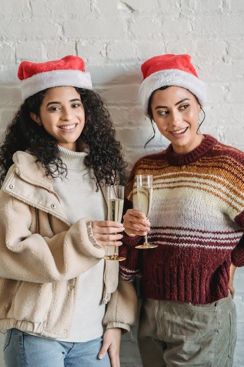 Smiling ethnic female with champagne celebrating Xmas
