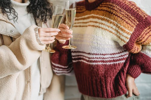 Crop faceless female friends in knitted sweaters clinking wineglasses of champagne during celebration together