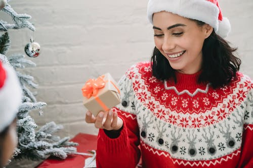 Smiling ethnic woman getting present box under Christmas tree