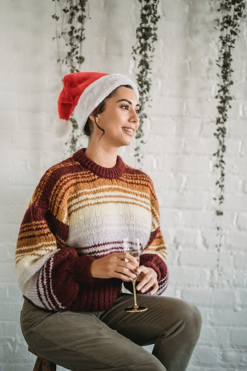 Smiling ethnic woman with glass of champagne during Christmas celebration