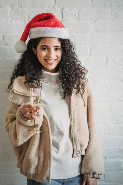 Cheerful ethnic woman in Santa hat with glass of champagne