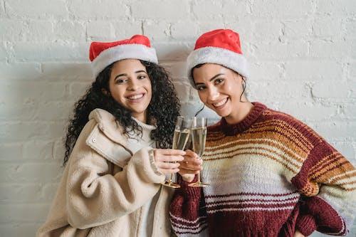 Happy ethnic women in Santa hats clinking champagne glasses
