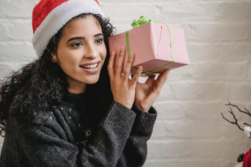 Smiling young ethnic female with curly hair wearing Santa hat and holding wrapped gift box near ear while looking away in excitement during Christmas party