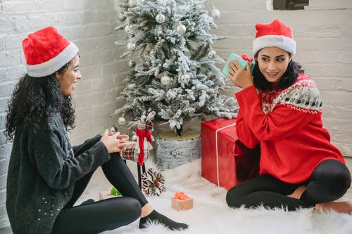 Ethnic women exchanging presents for Christmas holidays
