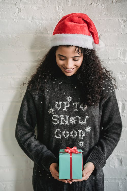 Smiling ethnic woman in Santa hat with present