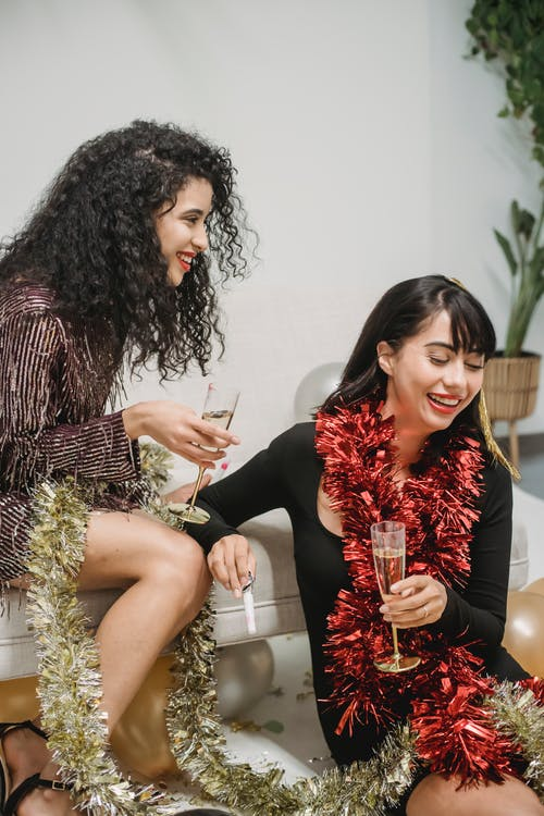 Laughing ladies drinking champagne during festive party