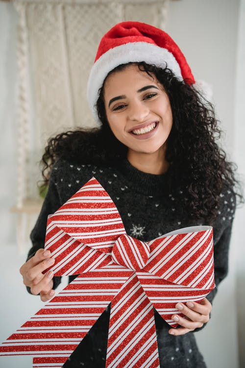 Smiling ethnic female with bow for Christmas decoration smiling widely and looking at camera