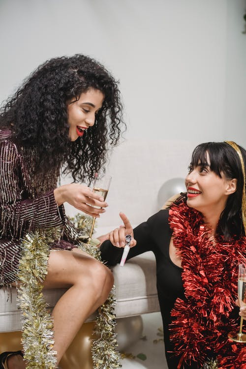 Positive ethnic females drinking champagne at Christmas party