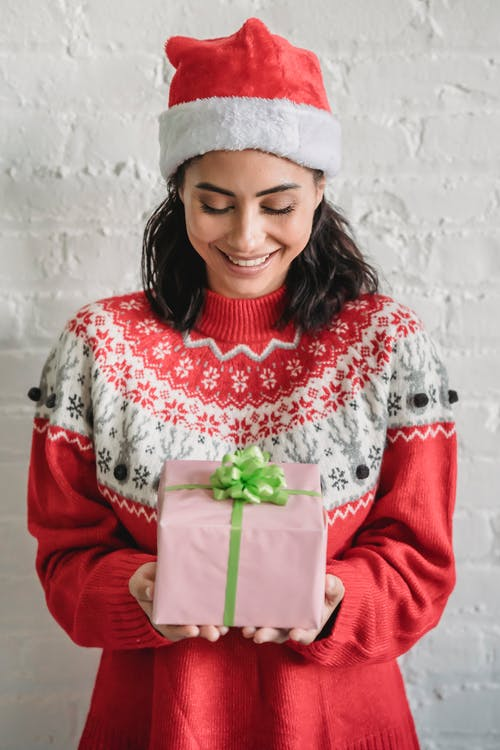 Smiling ethnic woman with Christmas gift decorated with bow