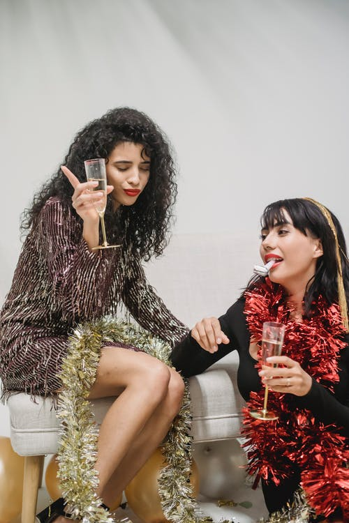 Woman with glass of champagne got drunk during New Year celebration with friend blowing party horn