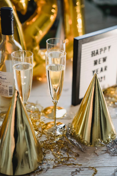 Champagne glasses and bottle near festive New Year decorations