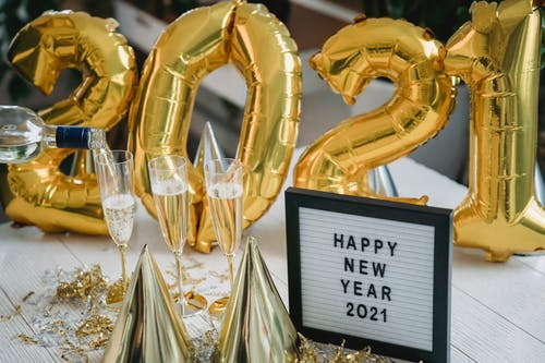 High angle of golden cone caps balloons and champagne in glasses near frame with Happy New Year 2021 inscription
