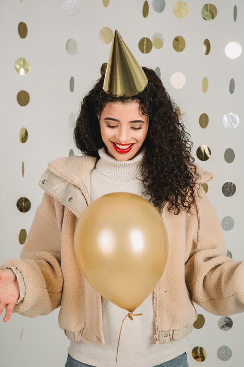 Smiling woman with balloon in decorated room