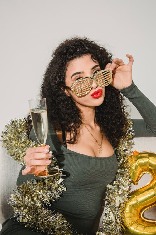 Glamour female with red lips in striped glasses with glass of champagne celebrating New Year