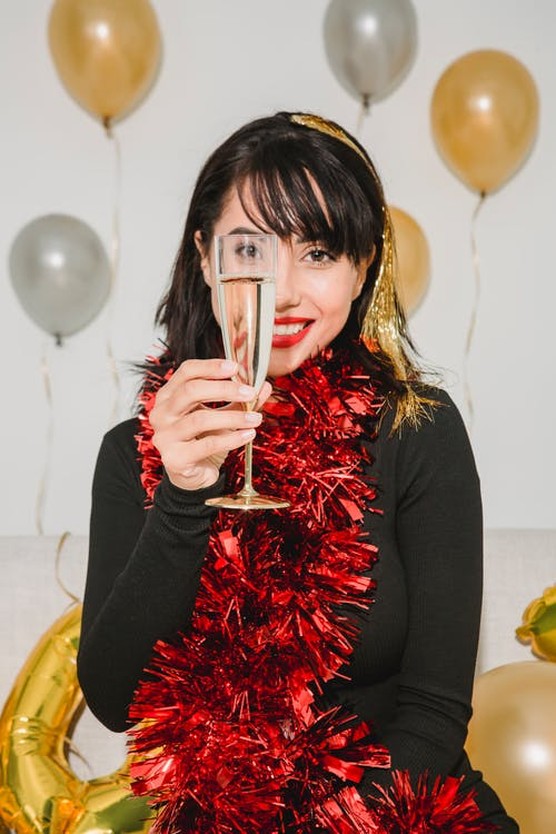 Cheerful female in red shimmering tinsel showing glass of champagne and smiling while looking at camera among balloons