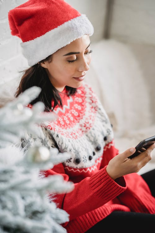 Woman in warm sweater and Santa hat checking smartphone