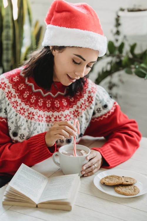 Happy smiling female in red Santa hat with cup of coffee with marshmallows and candy cane near plate with cookies