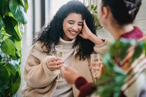 Happy ethnic young woman with glass of champagne laughing