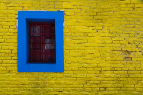 Blue Trim Around Window in Yellow Painted Stone Wall