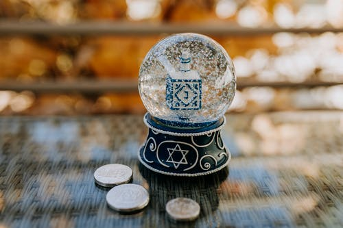 Close-Up Photo Of Snow Globe On Top Of Glass Table