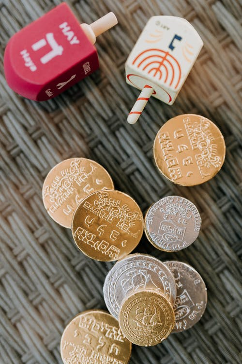 Close-Up Photo Of Dreidel Spinners Beside Gold Coins