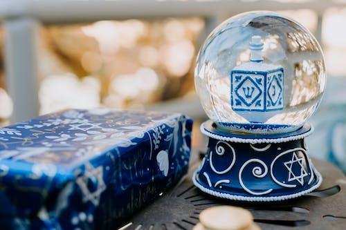 Close-Up Photo Of Snow Globe Beside Present