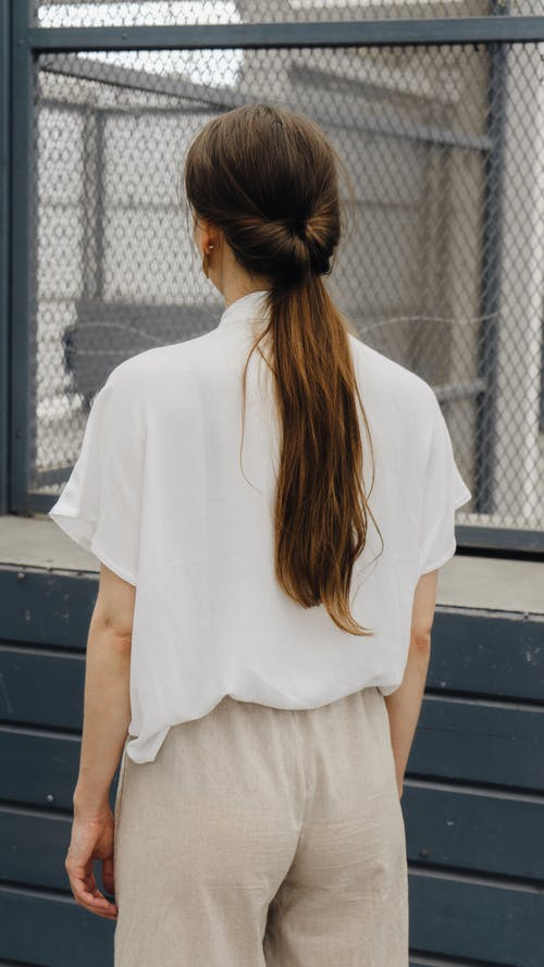 Unrecognizable young woman with long hair standing near building