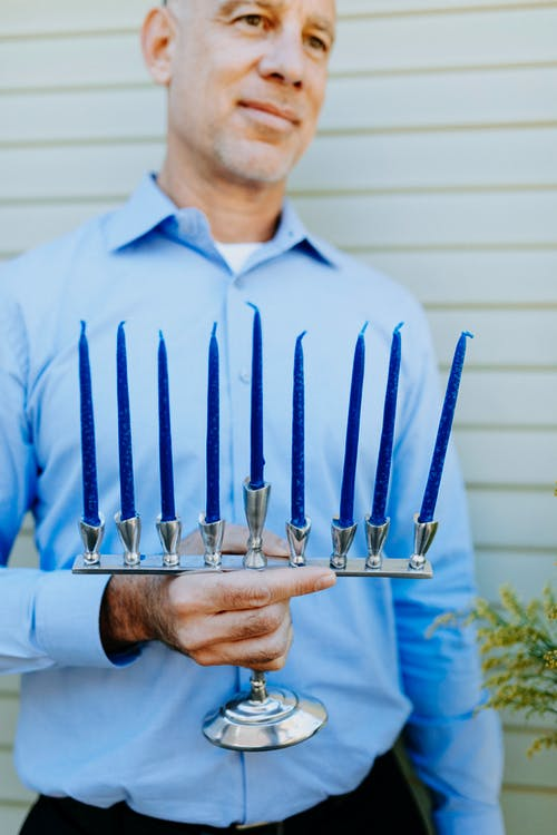 Photo Of Man Holding Candle Holder