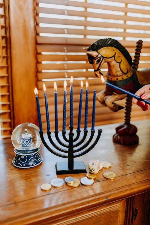 Foto Der Person, Die Eine Kerze Mit Angezündetem Kerzenhalter Anzündet