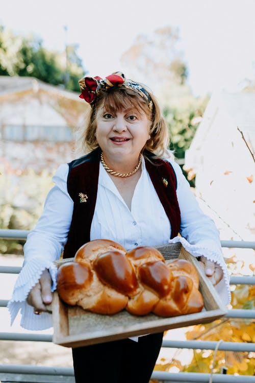 Photo Of Woman Holding A Brown Wooden Tray With Challah