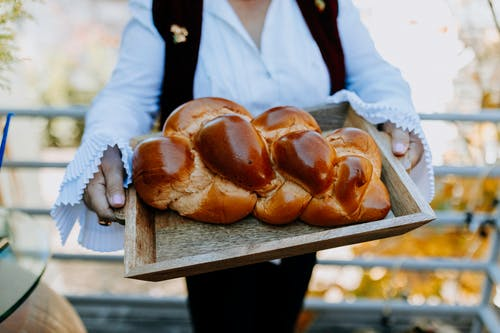 Close-Up Photo Of Person Holding A Tray Of Freshly Baked Bread