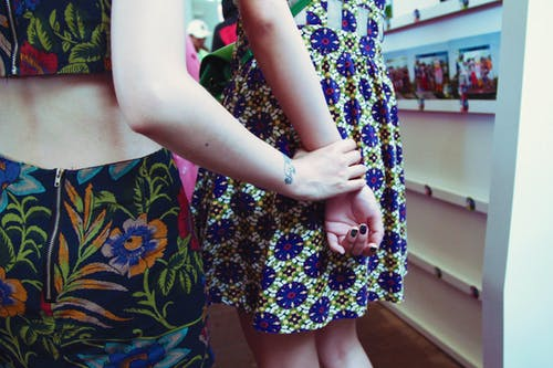 Back view of crop woman with tattoo in apparel with flower ornament touching arm of unrecognizable best female friend